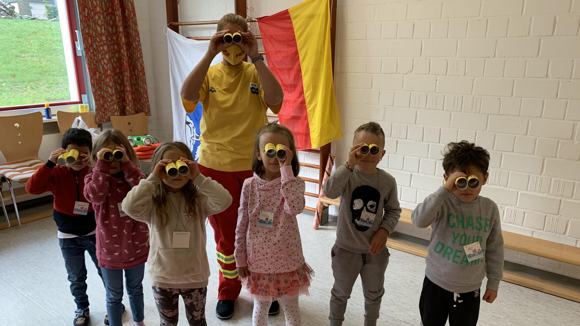 Die sechs Vorschulkinder und Teamerin Miriam Flackus schauen durch ihre selbstgebastelten Ferngläser.