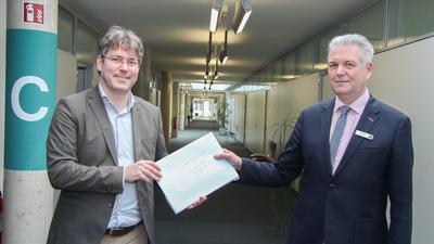 Zwei Männer in einem Flur mit einem Umschlag.