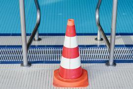 Eine Pylone steht im Hallenbad an einer Leiter des Schwimmerbeckens.
