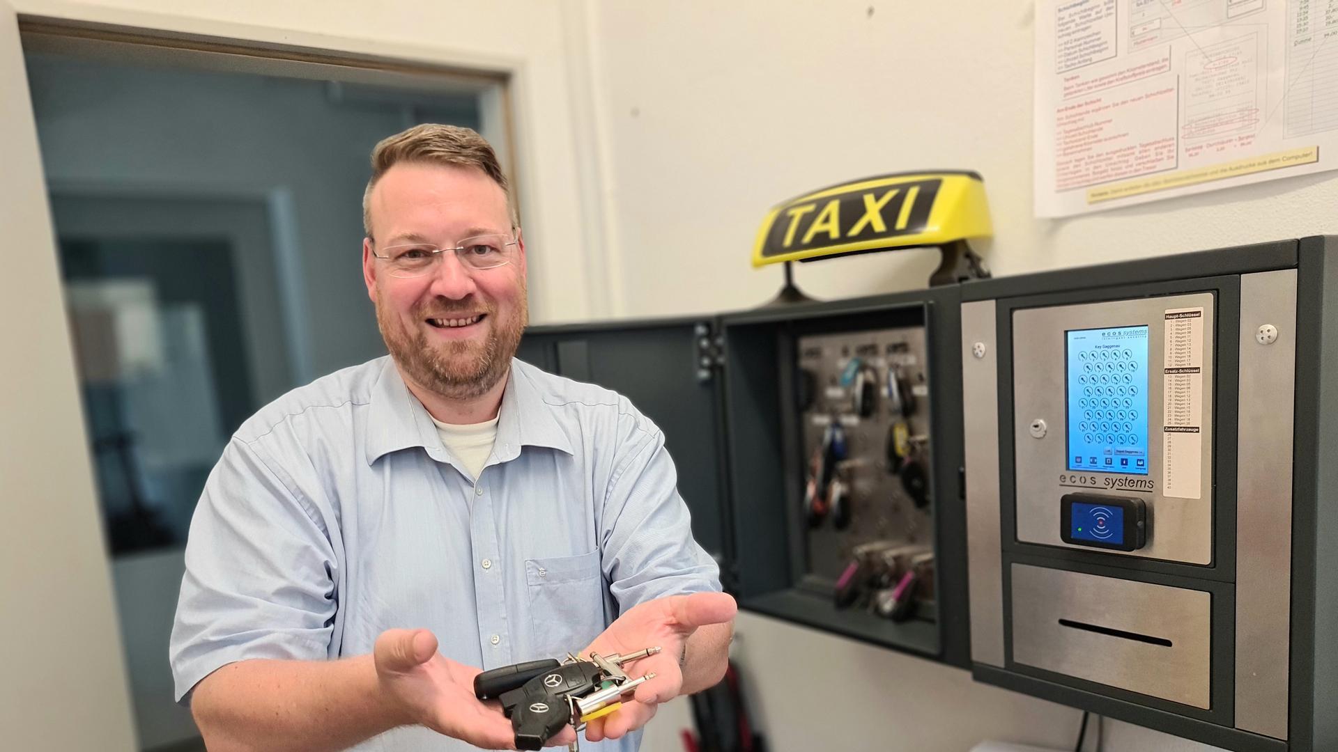 Ein Mann mit Autoschlüsseln in der Hand vor einem Tresor.