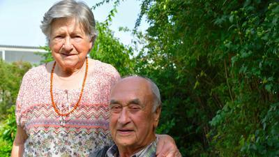 Älteres Ehepaar vor einem grünen Busch.