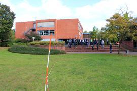 Hier könnte ab 2024 der Neubau entstehen: Bei der Schulbereisung am Dienstag kristallisierte sich die Freifläche neben der HLA-Sporthalle als Standort-Favorit heraus. Das Bild zeigt die Teilnehmer vor dem HLA-Gebäude.