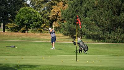 Golfspieler, Bälle, Bäume, Rasen