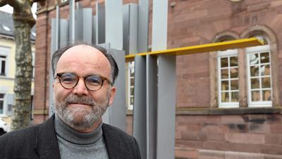 Ein Mann mit kurz geschnittenem grauem Bart steht vor einem Kunstwerk aus Metall.