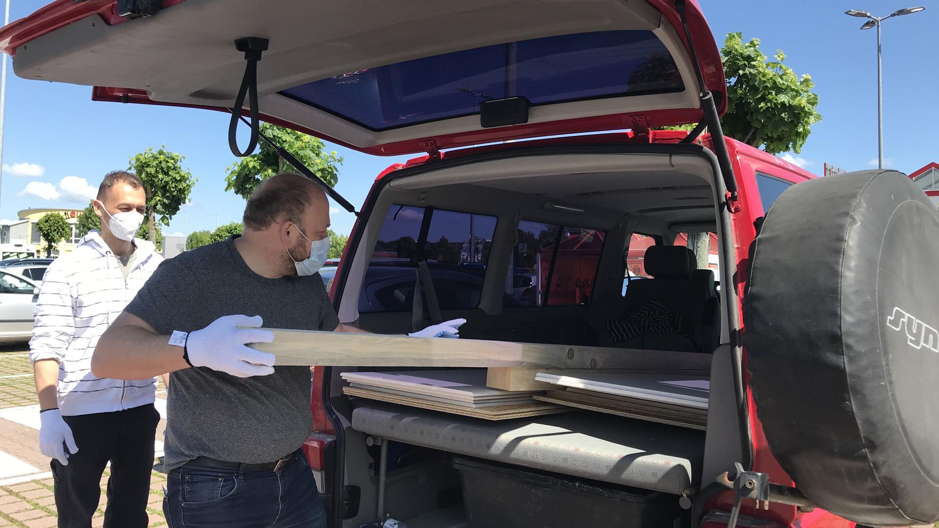 Ein Mann belädt einen Transporter mit Holzbalken