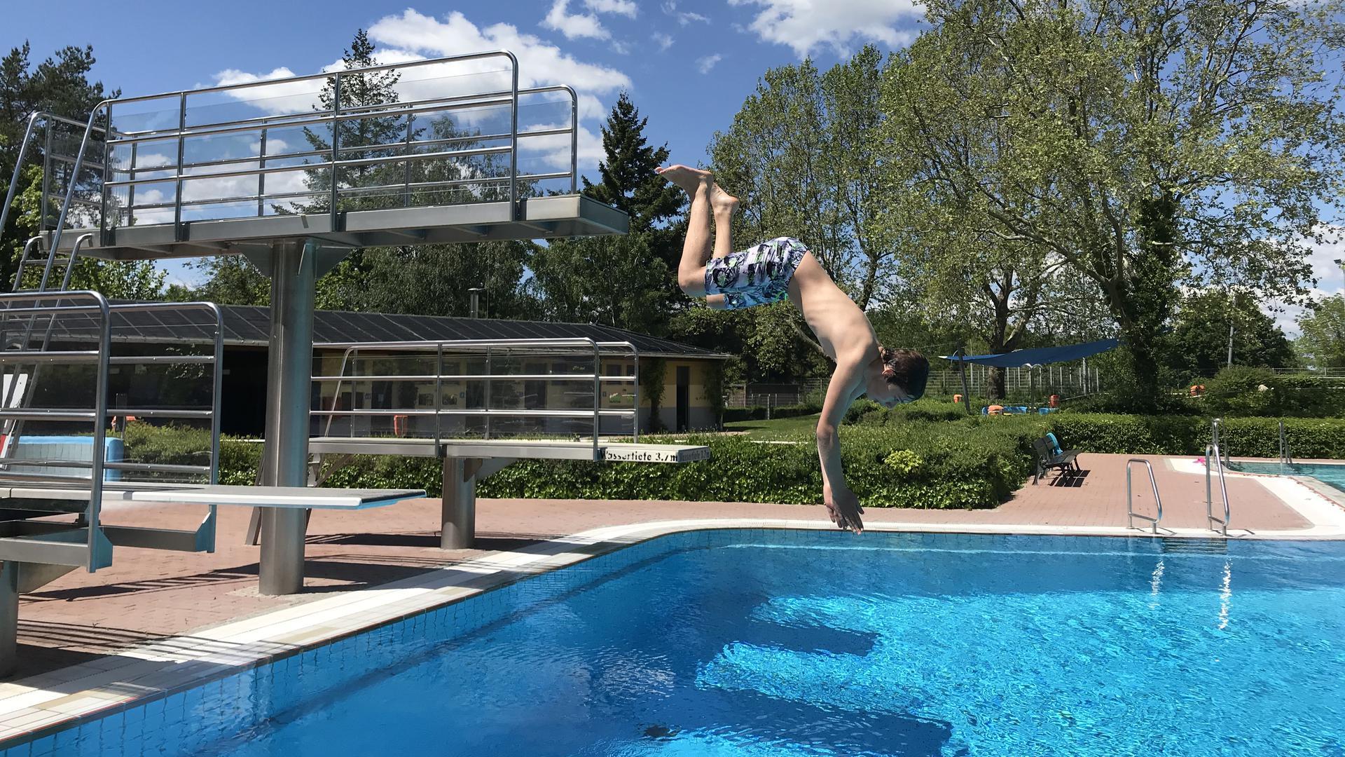 ein Junge springt kopfüber ins Wasser