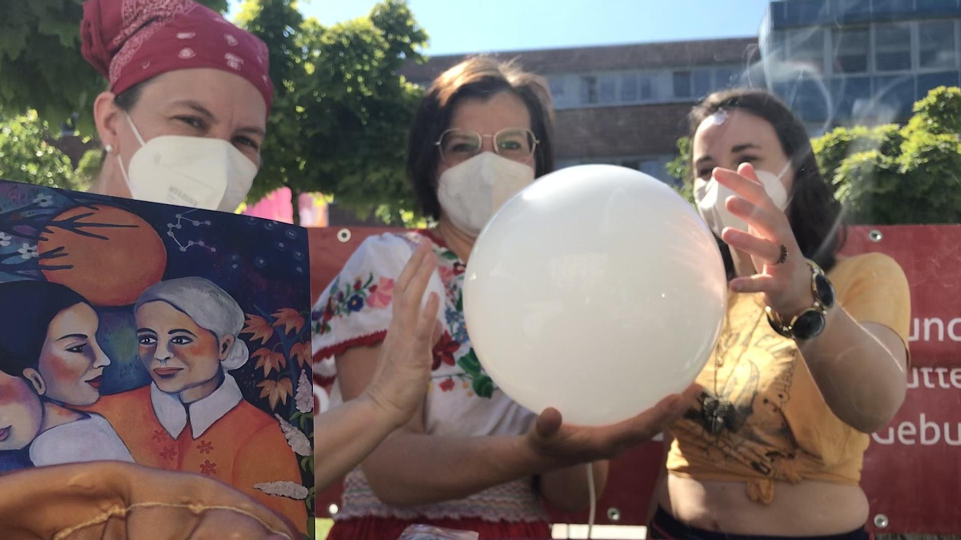 Drei Frauen schauen in eine Kristallkugel