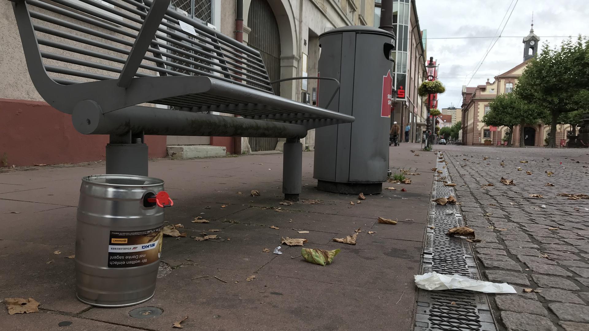 Müll an einer Sitzbank auf dem Rastatter Marktplatz, im Hintergrund das historische Rathaus
