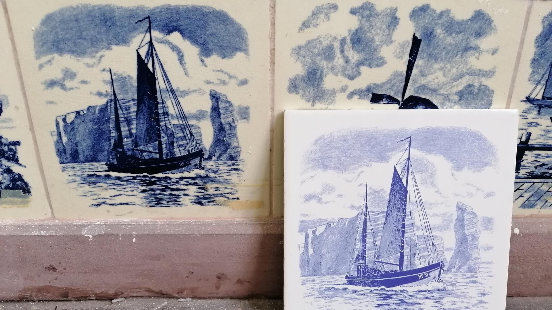 Links die Kachel aus der Pagodenburg, rechts das Erbstück von Manuel Sachse mit dem gleichen Motiv, das das Segelboot Maria HF 31 zeigt.