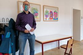 Schulleiter Christoph Nonnenmacher steht im Flur des Stammhauses der Pestalozzi-Schule Rastatt vor einem Tisch und einem Stuhl.