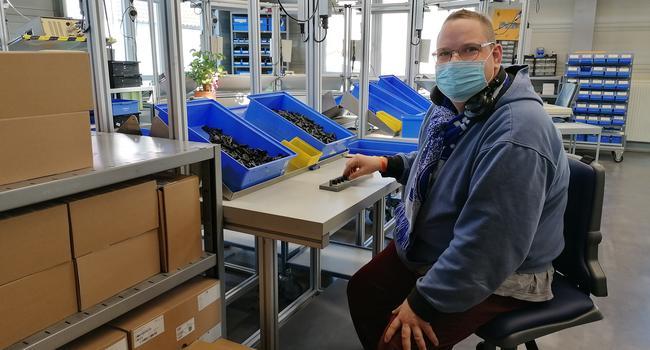 Matthias Rahner sitzt in einer Werkstatt an einem Tisch, auf dem mehrere, kleine, blaue Kisten stehen.