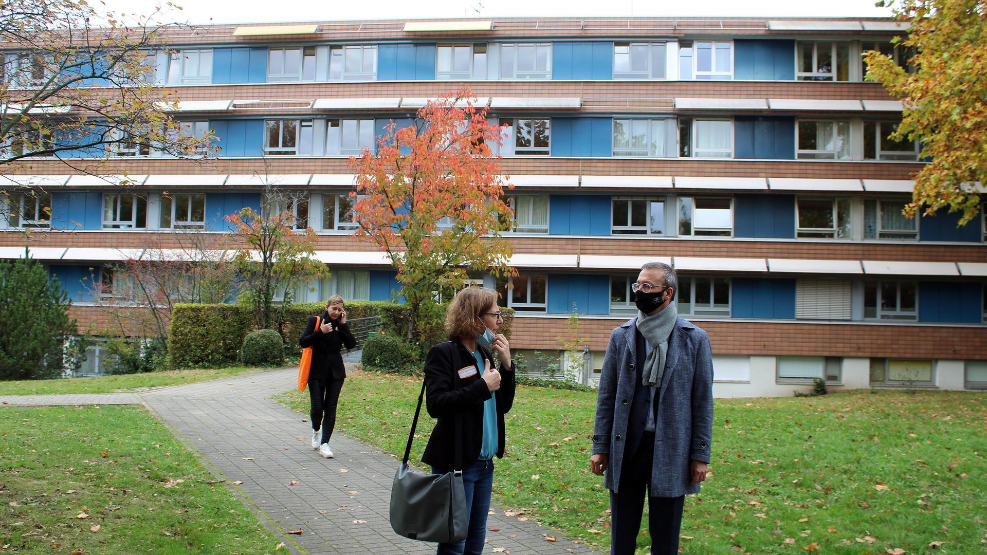 Drei Personen vor einem Gebäude.