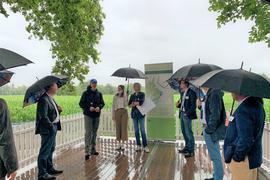 Leute mit  Regenschirmen, vor Infotafel  in freier Natur