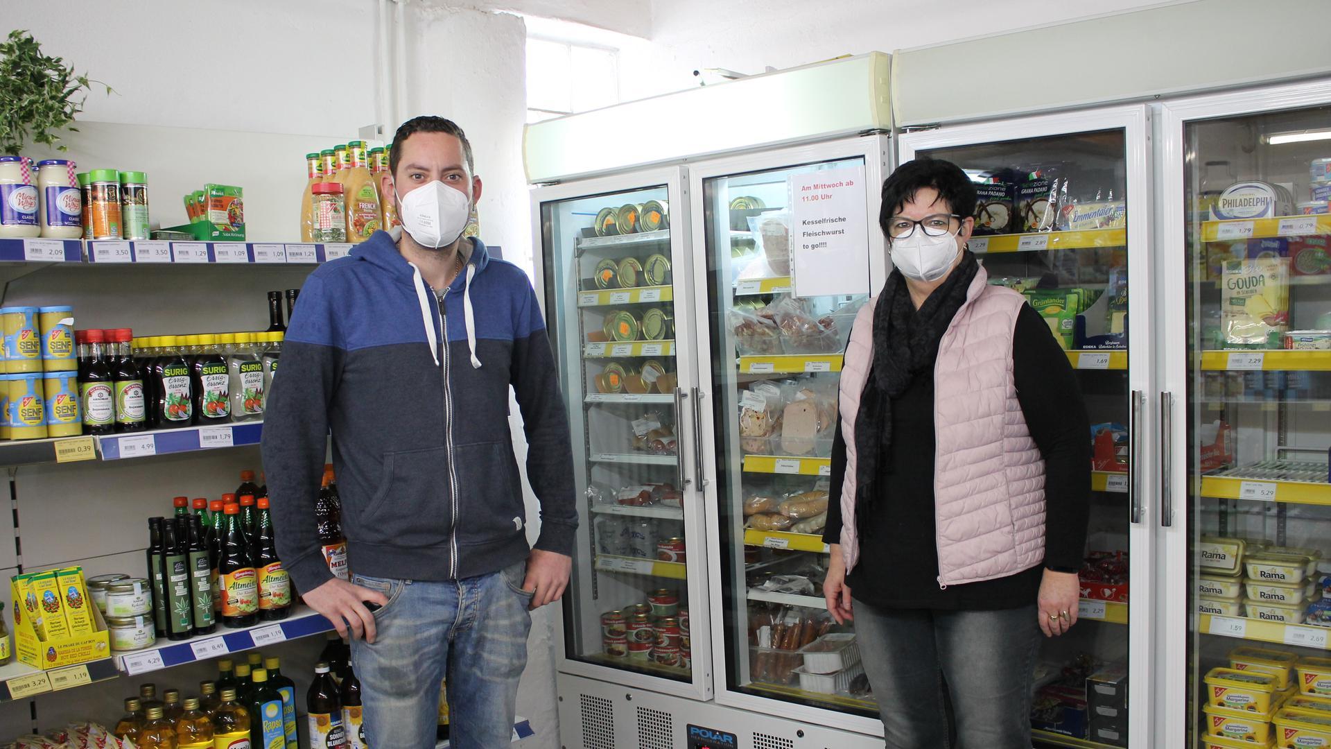 Links ein Mann, rechts eine Frau, dazwischen ein Kühlschrank mit Wurstwaren