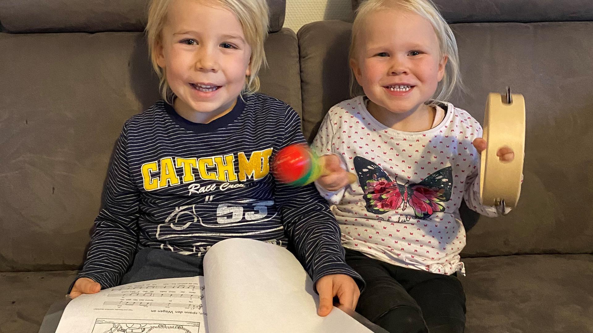 Zwei Kinder mit Liedermappe und Instrumenten auf einem Sofa