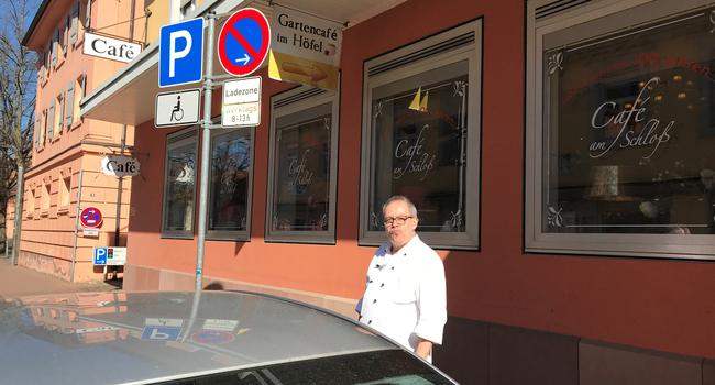 Ein Mann steht hinter einem geparkten Fahrzeug