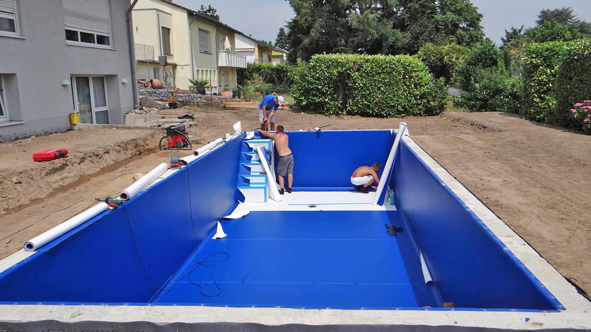 Schwimmbadbauer arbeiten in und an einem Becken.