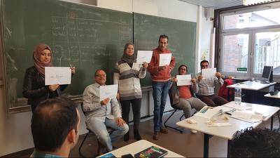 Teilnehmer eines Alphabetisierungskurses stehen an der Tafel.