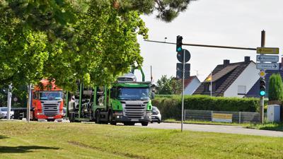 Zwei Lastwagen rollen direkt an Wohnhäusern vorbei. Mit einem Plakat fordern die Anwohner eine Querspange zur Entlastung.