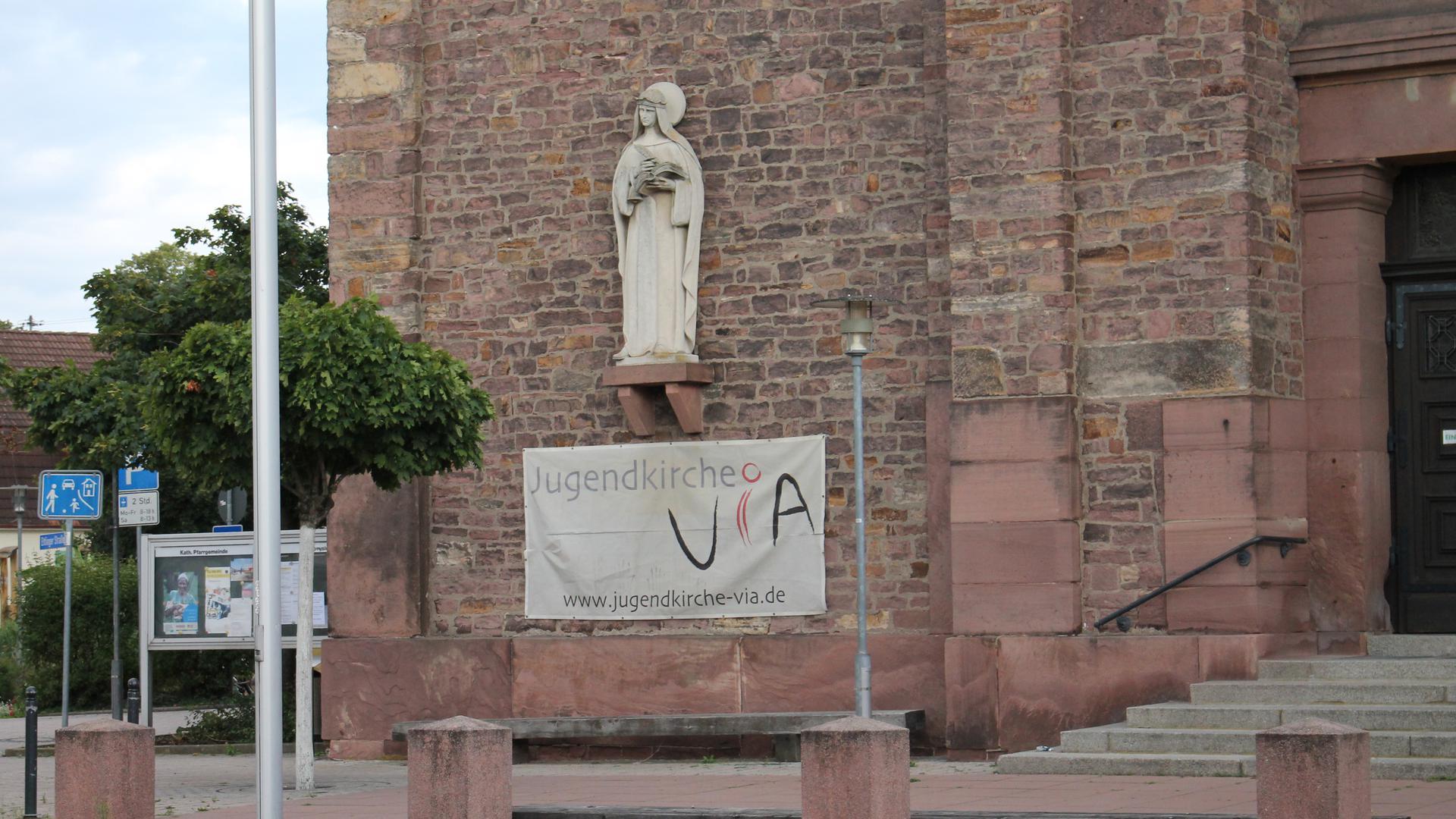 Kirchengemäuer mit Jugendkirche-Via Plakat und Mutter Gottes aus Stein