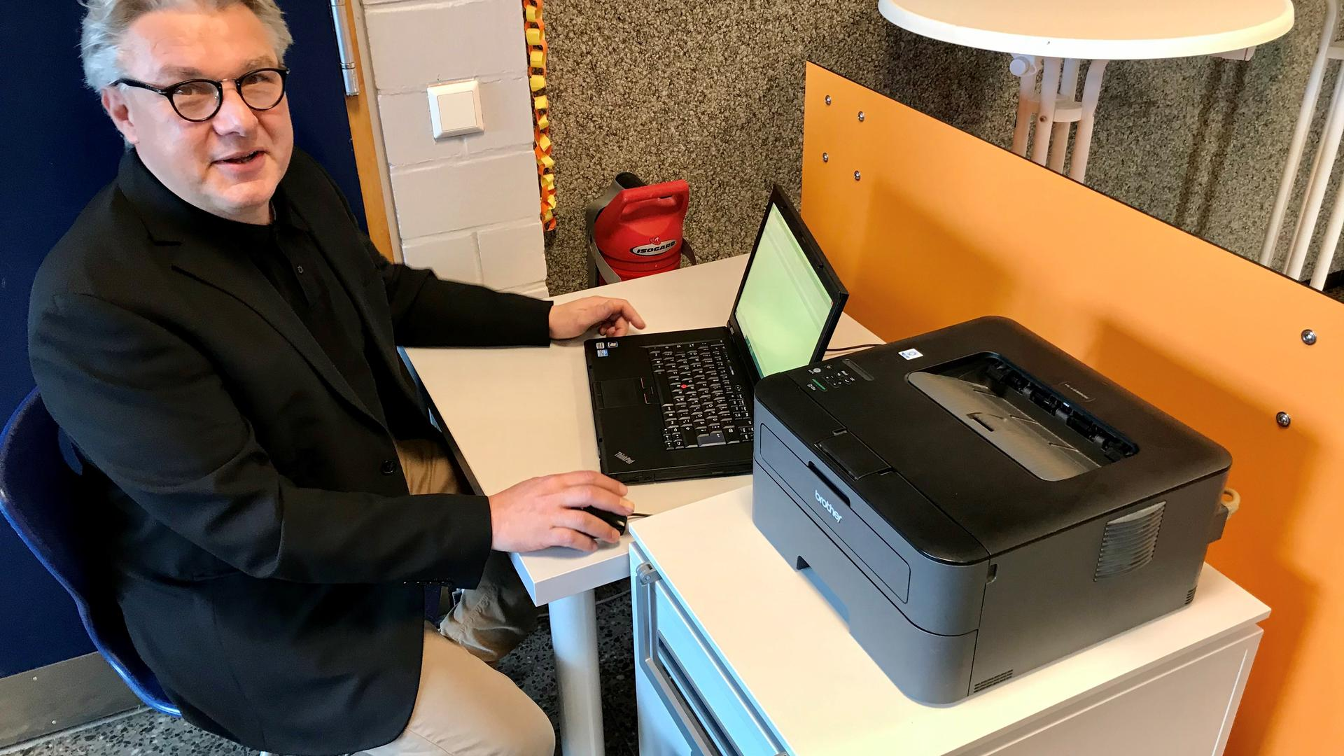 Schulleiter Volker Arntz sitzt in der Hardtschule in Durmersheim an einem Laptop, der an einen Drucker angeschlossen ist.
