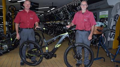 Zwei Männer mit einem Mountainbike im Fahrradladen
