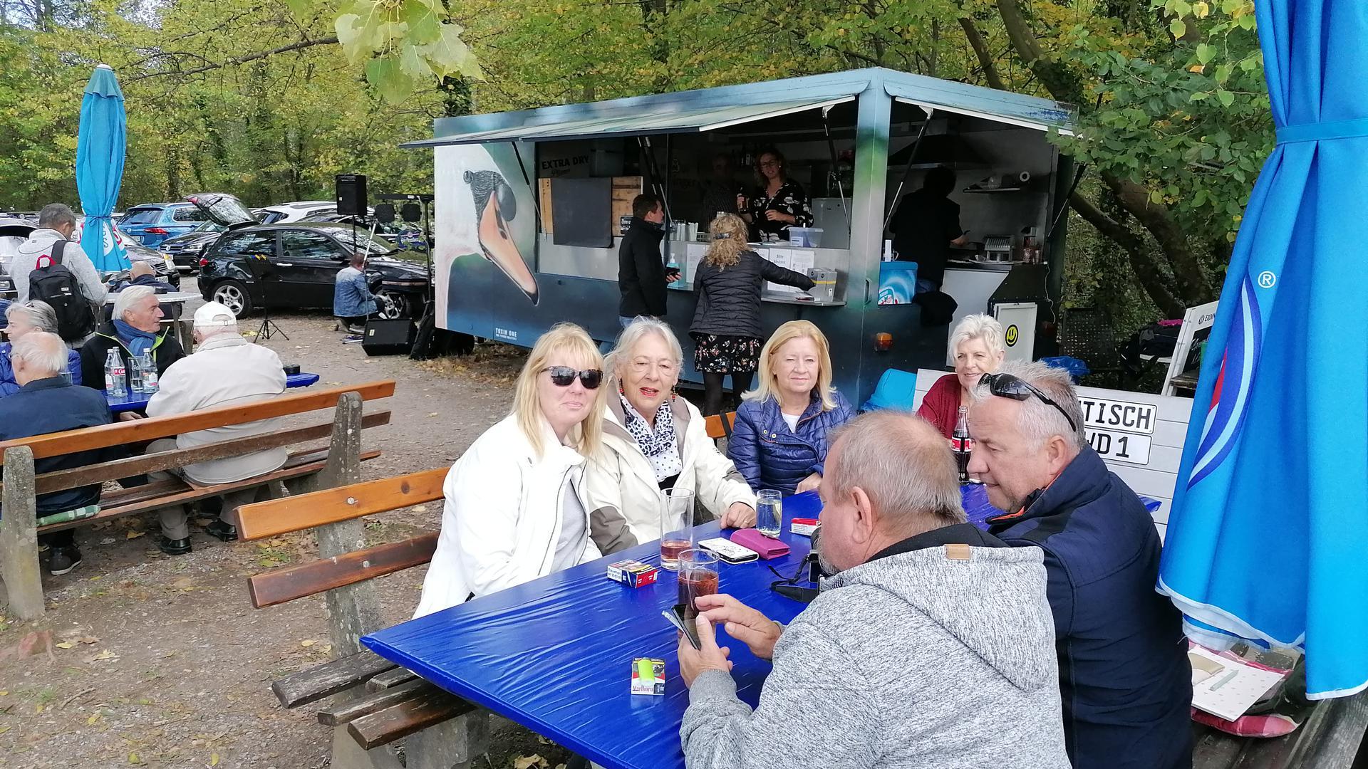 Vier Frauen und zwei Männer sitzen am Stammtisch, im Hintergrund ist der Kiosk-Anhänger zu sehen.