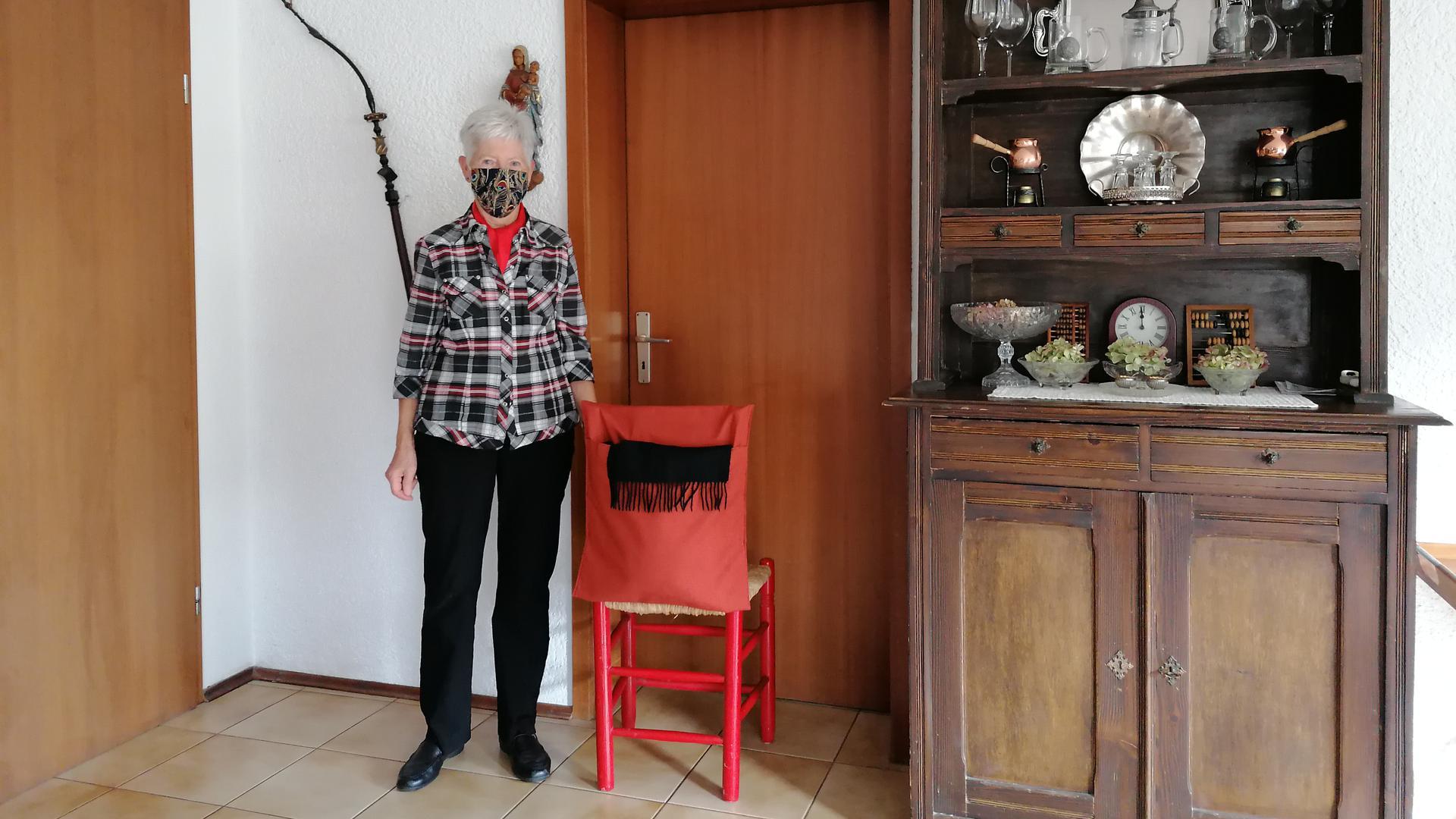 Marianne Fischer steht in ihrem Esszimmer neben einem Stuhl, über dessen Rückenlehne der selbstgenähte Rucksack hängt.
