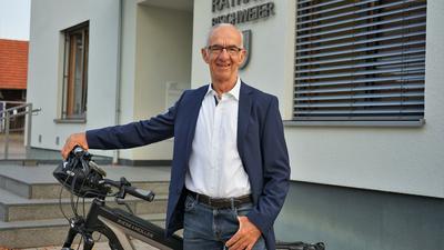 Ein Mann mit einem Fahrrad vor einem Gebäude.