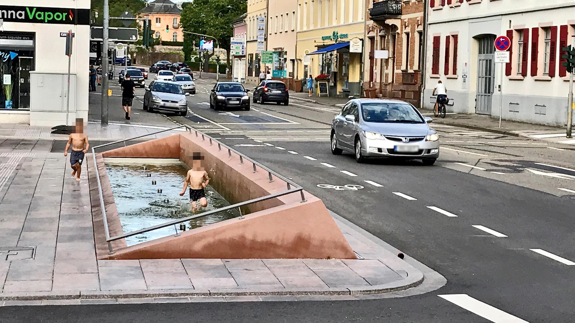 Ein Kind rennt durch einen Brunnen an einer Straße.