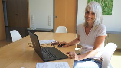 Eine Frau sitzt an ihrem Laptop