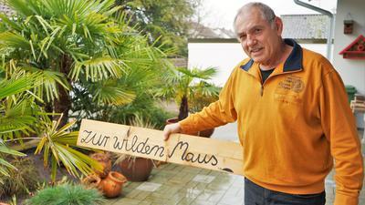 """Josef Kiefer zeigt ein Schild mit der Aufschrift """"Zur wilden Maus"""""""