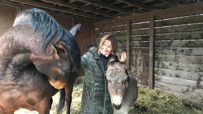 Eine Frau steht zwischen einem Pferd und einem Esel