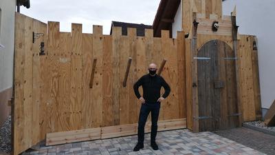 Marcel Lang steht vor einer aus Holzlatten gebauten Front, die eine Burg darstellt.