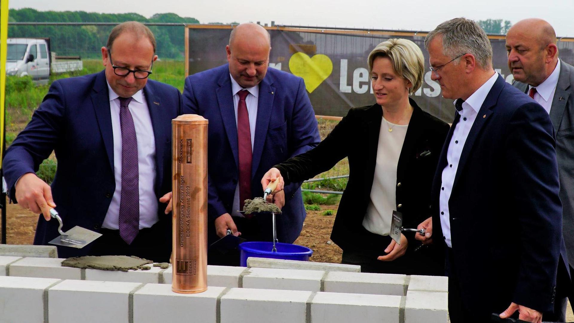 Eingemauert: Die Zeitkapsel installierten Ministerin Hoffmeister-Kraut, OB Pütsch (Zweiter von rechts) und Verantwortliche von Edeka fachgerecht.