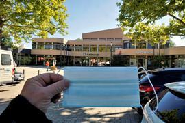Eine Mundschutzmaske vor einem Gebäude mit Rathaus und Apotheke.