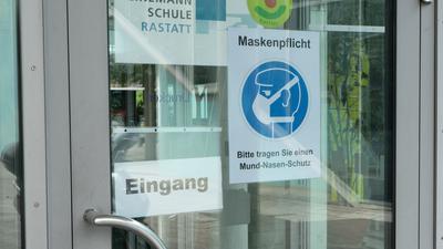 Das Bild zeigt den Eingang der Gustav-Heinemann-Schule. Ein Schild weist auf die bestehende Maskenpflicht hin.