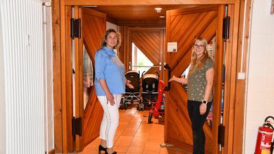 Zwei Frauen öffnen eine Türe.