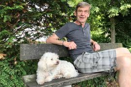 Ein Mann mit einem Hund auf einer Bank.