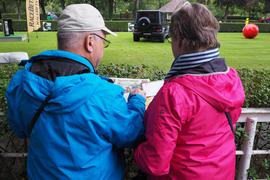 Bunte Farben gegen tristes Regenwetter: Zwei Besucher studieren am Führring das Rennprogramm.