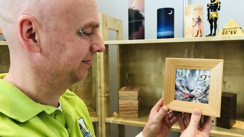 Christian Richers zeigt einen Holzbilderrahmen. Er ist aufklappbar. Im Innern könnte das Säckchen mit der Asche der verstorbenen Katze aufbewahrt werden.