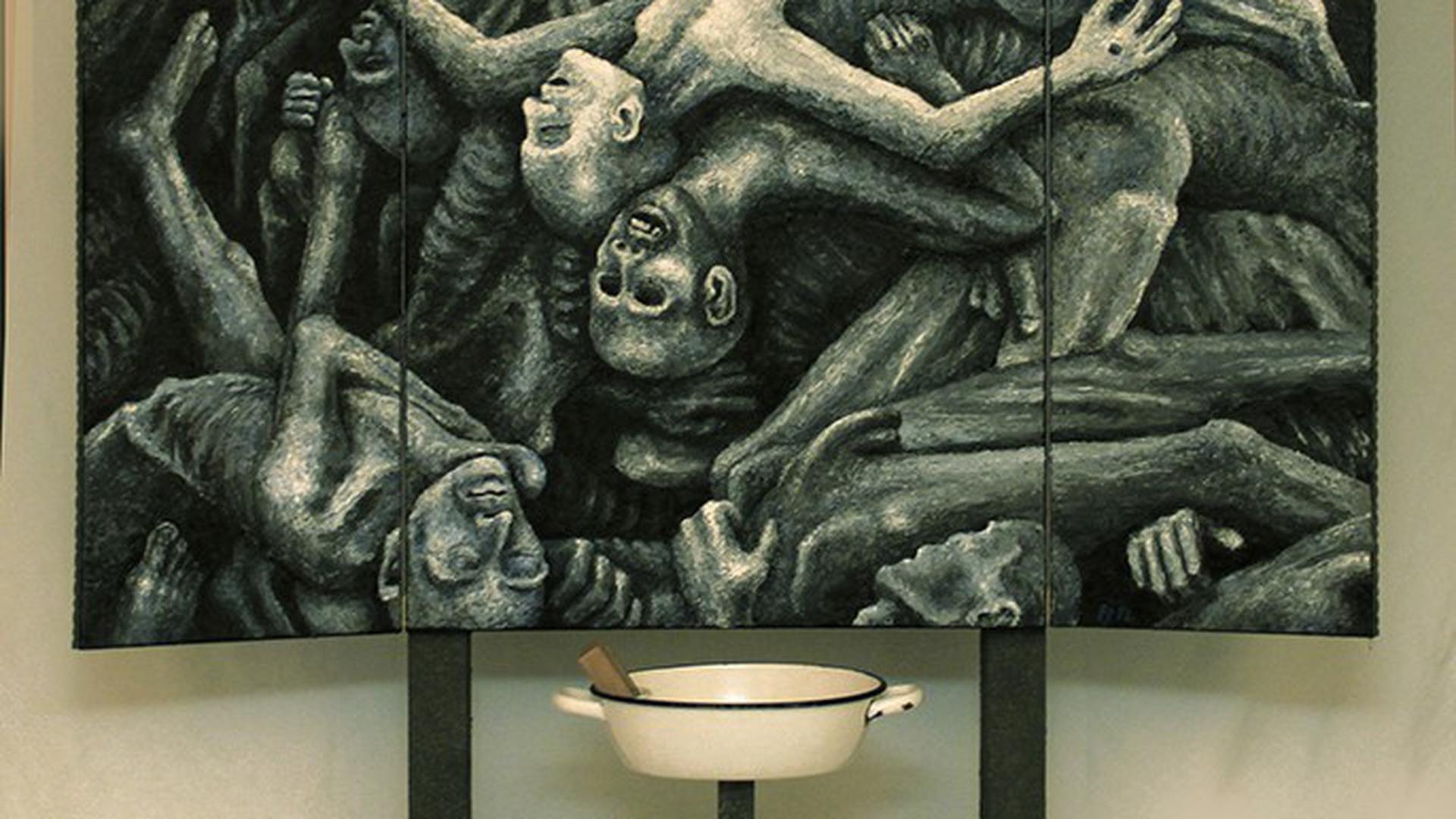 Vor einem Altar mit Stacheldraht und dem Bild eines Leichenhaufens steht eine Waschschüssel mit einem weißen Handtuch.