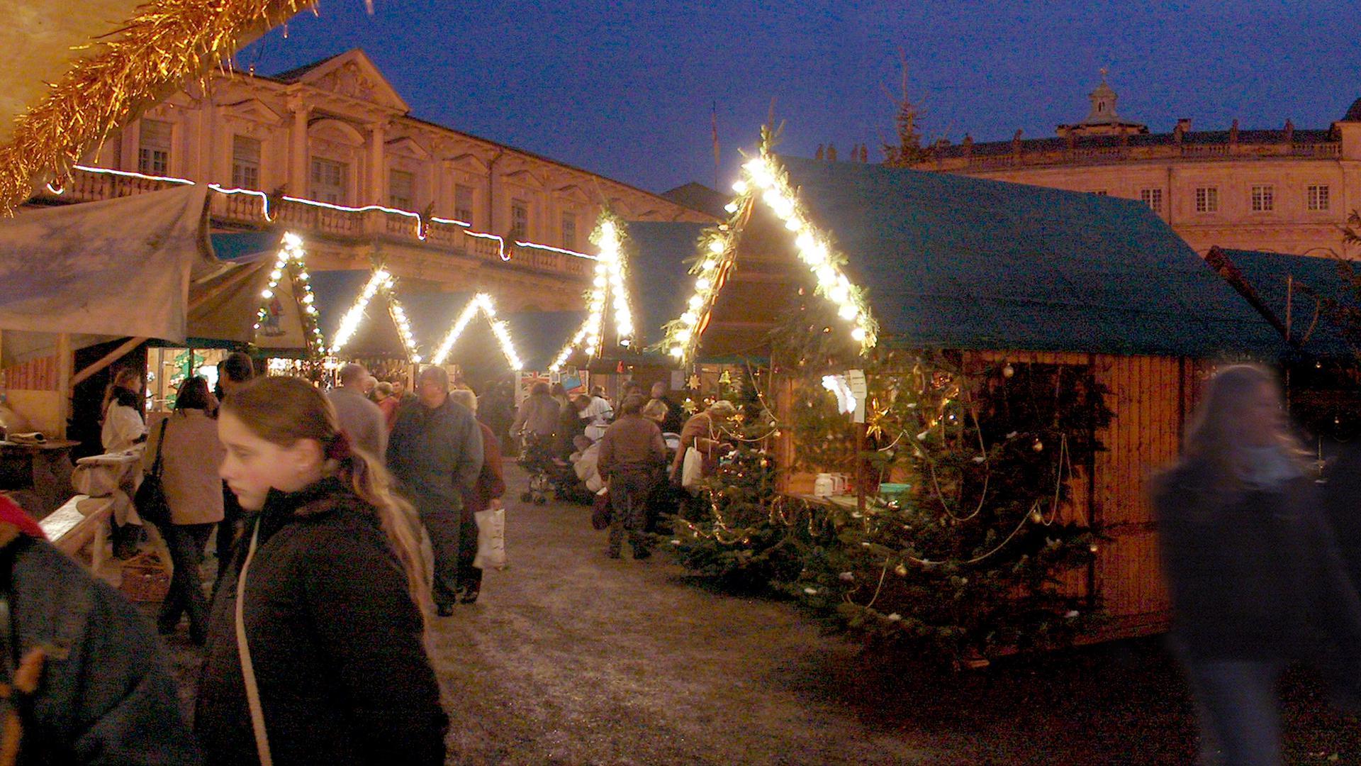 Menschen laufen über die Schlossweihnacht vor dem Barockschloss in Rastatt.