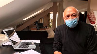 Ein Mann mit einer Schutzmaske an einem Schreibtisch.