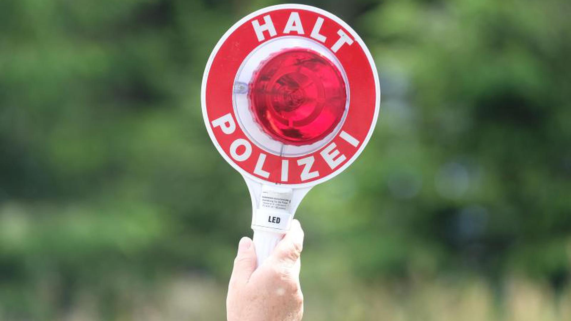 Eine Polizisten hält eine rote Winkerkelle in die Höhe