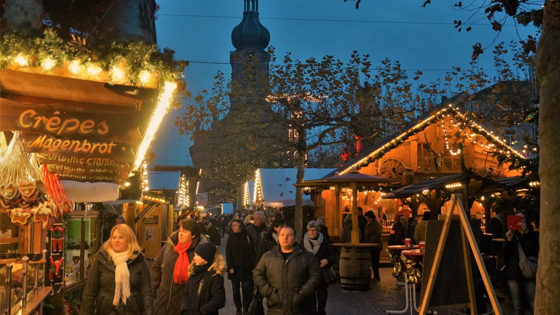 Menschen laufen an den Buden vorbei über den Weihnachtsmarkt in Rastatt.
