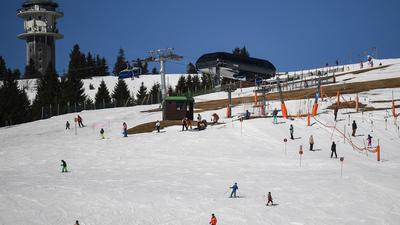 Skifahrer und Snowboarder fahren eine Piste auf dem Feldberg hinunter.