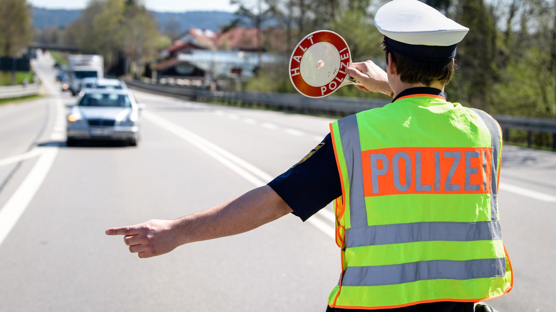 18.04.2018, Bayern, Wolfratshausen: Ein Polizist winkt ein Fahrzeug von der Bundesstraße zu einer Kontrollstelle der Polizei auf den Standstreifen. In mehreren Bundesländern führt die Polizei an diesem Tag beim Blitzmarathon über 24 Stunden vermehrt Geschwindigkeitskontrollen durch. Rund 1900 Polizisten werden bayernweit an 2000 Stellen die Geschwindigkeit messen und Raser aus dem Verkehr ziehen. Foto: Matthias Balk/dpa ++ +++ dpa-Bildfunk +++