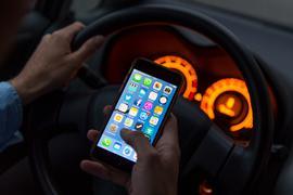 Ein Mann sitzt in einem Auto am Steuer und hält ein Smartphone in der Hand.