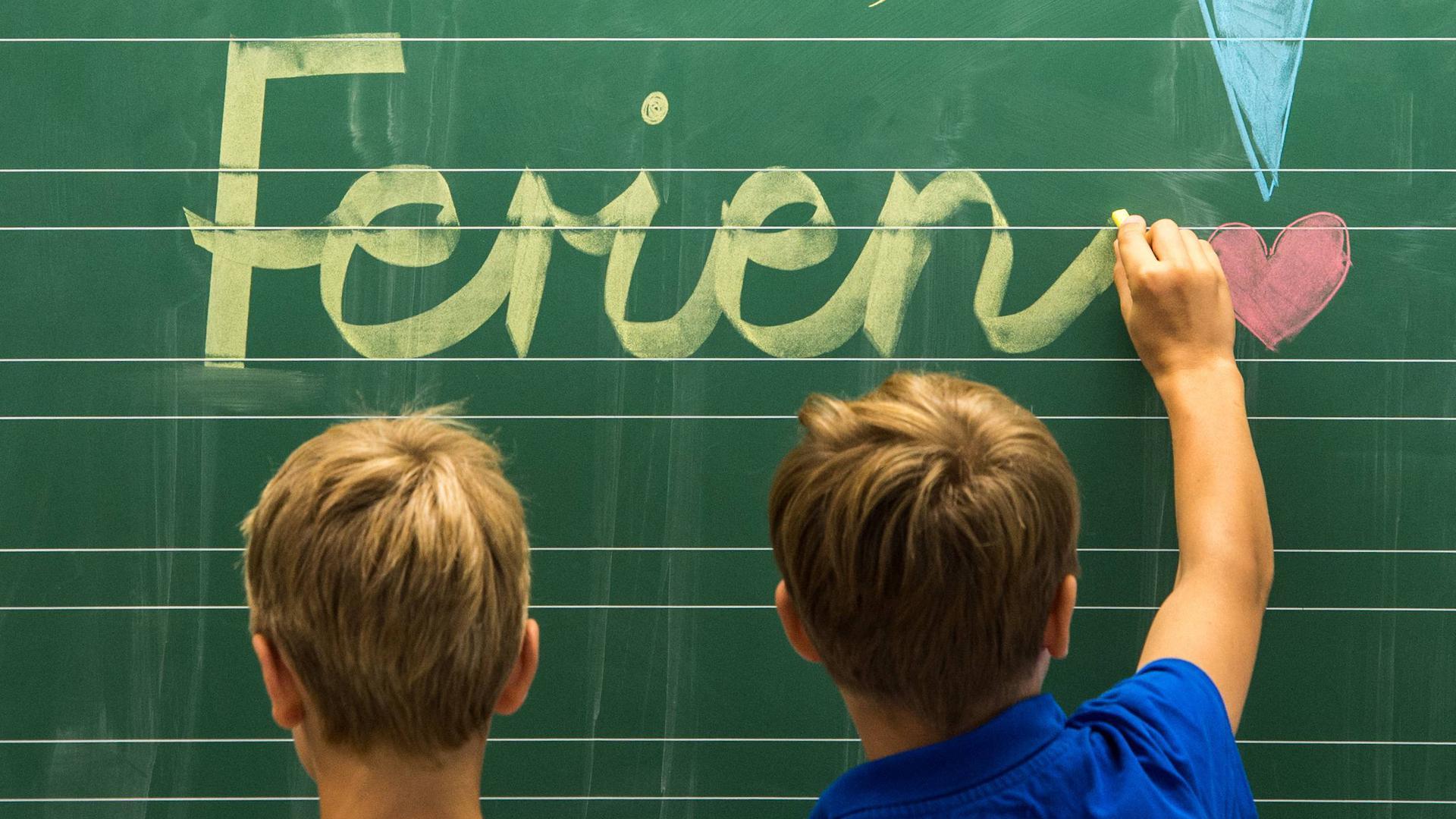 """Ein Junge schreibt mit Kreide """"Ferien"""" auf eine Tafel."""